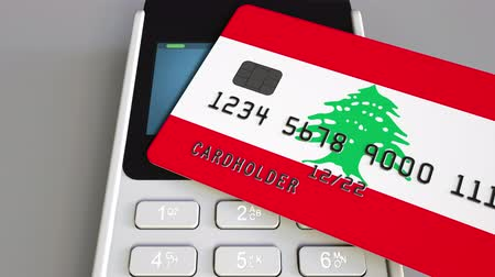 payment terminal : Payment or POS terminal with credit card featuring flag of Lebanon. Lebanese retail commerce or banking system conceptual animation