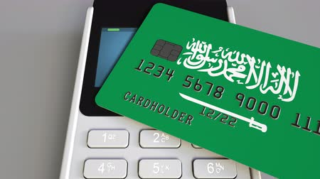 payment terminal : Payment or POS terminal with credit card featuring flag of Saudi Arabia. Retail commerce or banking system conceptual animation Stock Footage
