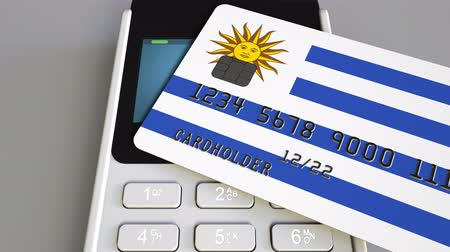 payment terminal : Payment or POS terminal with credit card featuring flag of Uruguay. Uruguayan retail commerce or banking system conceptual animation