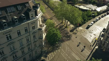 crossing road : Aerial view of people riding bikes along sunny street in Leipzig, Germany Stock Footage