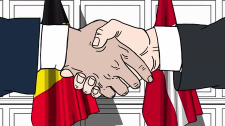 бельгийский : Businessmen or politicians shake hands against flags of Belgium and Denmark. Official meeting or cooperation related cartoon animation Стоковые видеозаписи