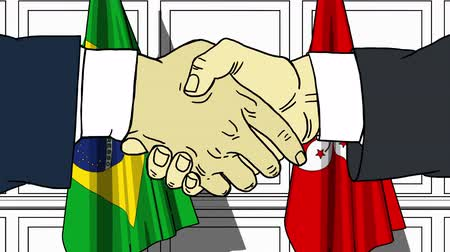 colaboração : Businessmen or politicians shake hands against flags of Brazil and Hong Kong. Official meeting or cooperation related cartoon animation