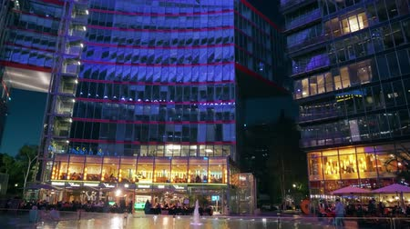éjszakai élet : BERLIN, GERMANY - APRIL 30, 2018. Sony Center inner courtyard in the evening Stock mozgókép