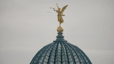 saxon : Airplane flying behind golden statue of Pheme or Fama on top of the glass dome of the Dresden Academy of Fine Arts