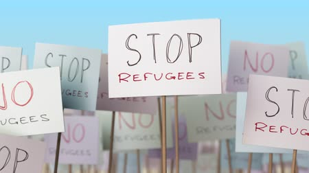 picketing : STOP REFUGEES placards at street demonstration. Conceptual loopable animation