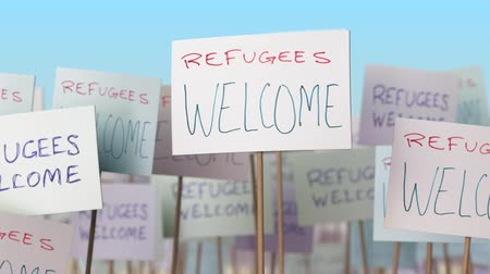 gösterici : REFUGEES WELCOME placards at street demonstration. Conceptual loopable animation