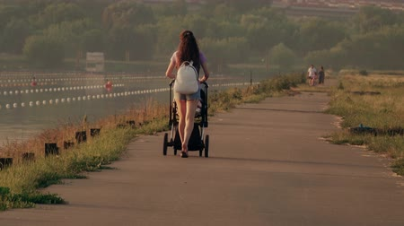 толчок : Beautiful young woman pushing stroller along waterfront pathway