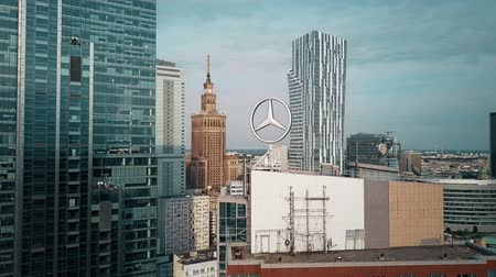 varšava : WARSAW, POLAND - JUNE 27, 2018. Aerial shot of rotating Mercedes-Benz logo within downtown cityscape