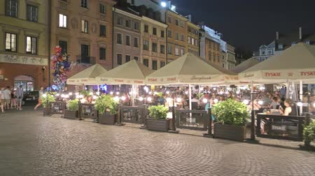 veranda : WARSAW, POLAND - AUGUST 4, 2018. Restaurant in a tourist place in the evening Stock mozgókép