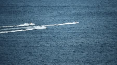 jet ski : Three distant jet ski riders at sea, slow motion shot