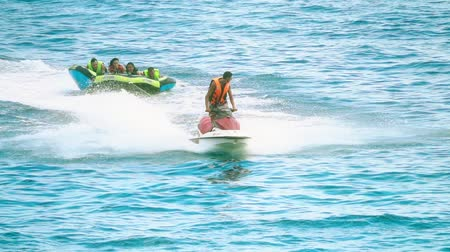 jet ski : BUDVA, MONTENEGRO - JULY 26, 2018. People have fun riding inflatable raft towed by jet ski, slow motion shot
