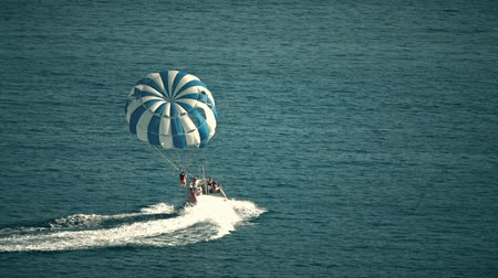 ascensão : BUDVA, MONTENEGRO - JULY 26, 2018. Parasailing parachute and speedboat at sea