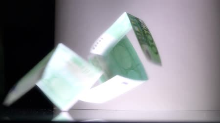 konkurzu : Slow motion shot of crumbling house made of euro notes. Mortgage or construction problem concepts