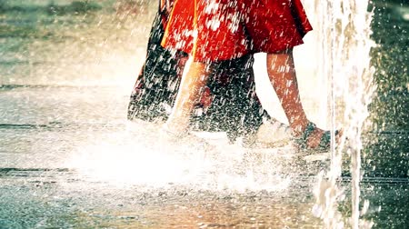 wetness : Slow motion video of two young women walking in park fountain on a hot summer day Stock Footage