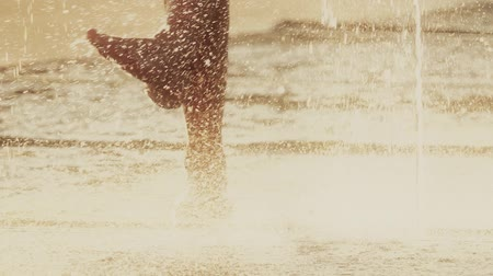 wetness : Slow motion shot of barefooted person in a fountain on a hot summer day