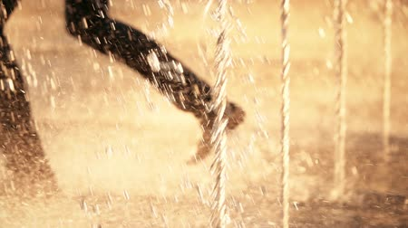 wetness : Slow motion shot of defocused barefooted person running in a fountain on a summer day