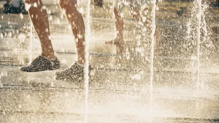 wetness : Slow motion video of people walking in fountain on a summer day Stock Footage
