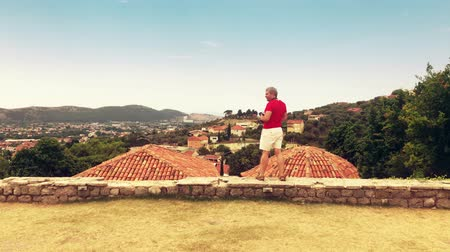 fotoğrafçı : Man takes photo of ancient architecture in Montenegro on vacation