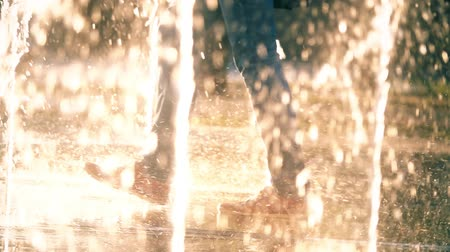 wetness : Slow motion shot of person walking in a fountain Stock Footage