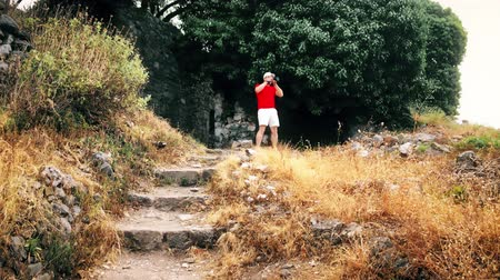 photoshoot : Man in red tshirt takes landscape photos with his camera on vacation