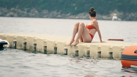 pontão : Beautiful woman in red bikini sits on floating pontoon at sea Vídeos