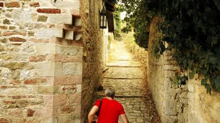 passagem : Male traveler in red tshirt walks in ancient Mediterranean fortress on vacation Vídeos