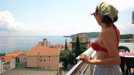 erkély : Beautiful woman looks at sea from the terrace on a summer day