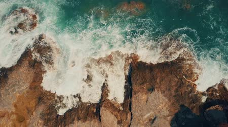 Aerial top down view of foamy sea surf on rocks