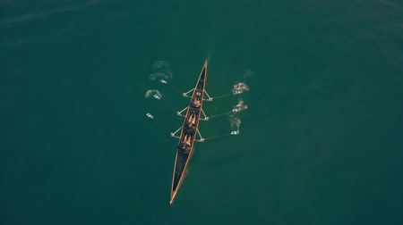 экипаж : Aerial down view of three unknown people rowing in a boat