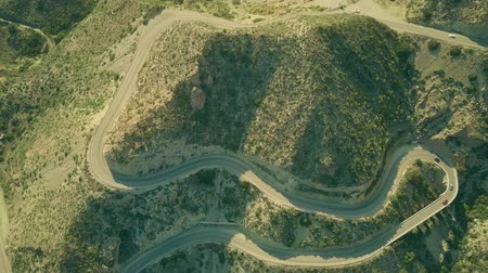 вокруг : Aerial top down shot of a windy car road in mountainous area Стоковые видеозаписи