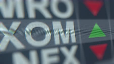 invest : EXXON MOBIL XOM stock ticker on the screen. Editorial loopable animation Stock Footage