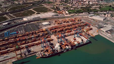 海港 : VALENCIA, SPAIN - OCTOBER 2, 2018. Aerial view of MSC container ship and seaport cranes at work 動画素材