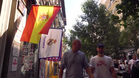 real madrid : MADRID, SPAIN - SEPTEMBER 30, 2018. Flags of Spain and Real Madrid football club above crowded tourist street in city centre Stock Footage