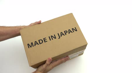 reciclado : Man gives box with MADE IN JAPAN text on it