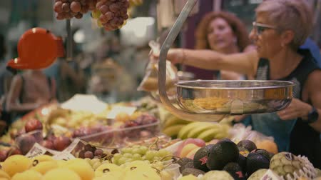 tartmak : VALENCIA, SPAIN - SEPTEMBER 22, 2018. Customers and vendors at fruit stall in famous Mercado Central or Central Market Stok Video