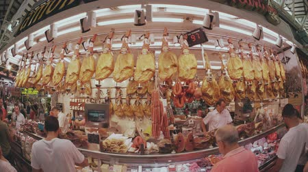 sorteren : VALENCIA, SPANJE - SEPTEMBER 22, 2018. Fish-eye lens weergave van jamon en andere Spaanse vleesspecialiteiten kraam in Mercado Central of Central Market