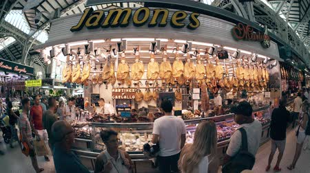 stragan : VALENCIA, SPAIN - SEPTEMBER 22, 2018. Fish-eye lens view of jamon meat specialties stall in Mercado Central or Central Market Wideo