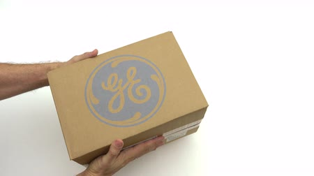 general electric : Hands holding box with GENERAL ELECTRIC logo. Editorial clip