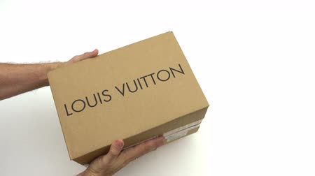 изолированные на белом : Man holding carton with LOUIS VUITTON logo. Editorial clip
