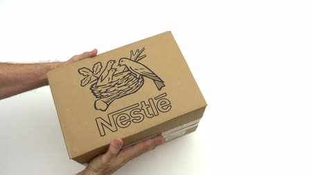 reciclado : Man holding carton with NESTLE logo. Editorial clip Stock Footage