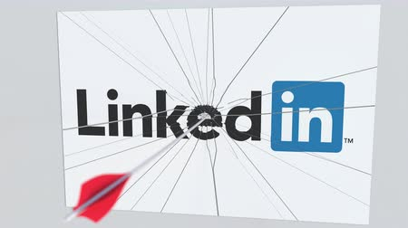 culpa : LINKEDIN company logo being cracked by archery arrow. Corporate problems conceptual editorial animation