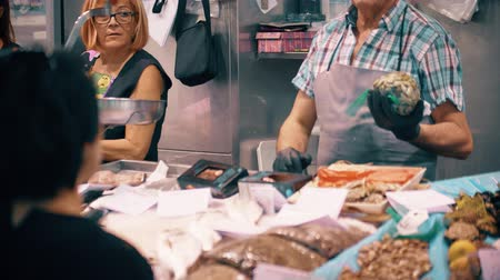 puhatestű : VALENCIA, SPAIN - SEPTEMBER 22, 2018. Customer and vendor at seafood stall in famous Mercado Central or Central Market