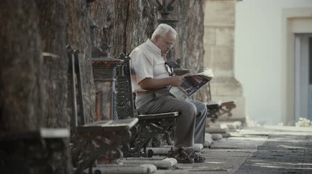 spaniard : VALENCIA, SPAIN - SEPTEMBER 22, 2018. Elder man sitting on park bench and reading newspaper