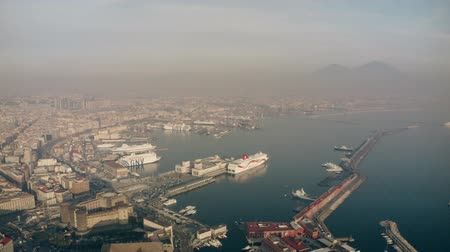 neapol : NAPLES, ITALY - DECEMBER 29, 2018. Aerial view of the city seaport area and distant Mount Vesuvius in the haze
