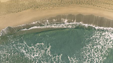 ślady stóp : Aerial top down view of sea surf on sand beach with many footprints