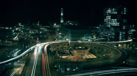nowoczesne : Lighthouse and city interchange traffic in seaport area of Genoa, Italy, at night. Long exposure time lapse