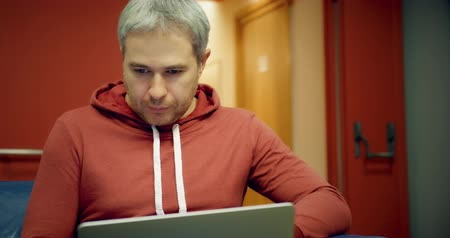 előcsarnok : Young smart grey haired man in casual clothes uses his laptop in the lobby
