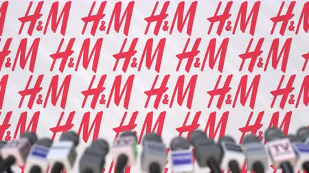 declaring : News conference of H&M, press wall with logo as a background and mics, editorial animation