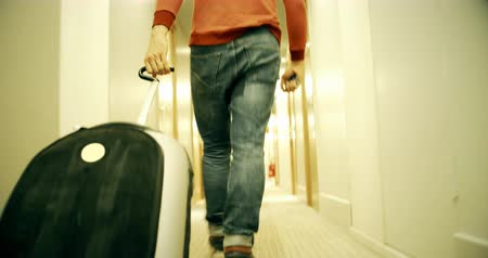 doorway : Man in jeans with suitcase walks along the hotel hallway