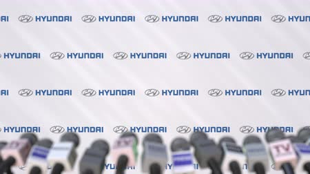 declaring : HYUNDAI company press conference, press wall with logo and mics, conceptual editorial animation